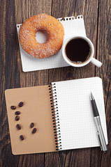 Notebook and cup of coffee with donut