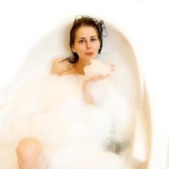 Pretty girl lies naked in a bathtub with foam
