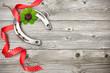 Horseshoe, shamrock and red ribbon on old wooden