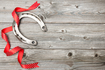Horseshoe with red ribbon on old wooden