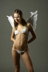 Beautiful slim model in a white bikini with wings
