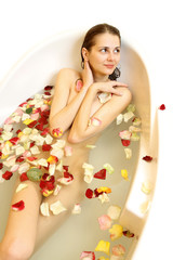 Attractive cute naked girl taking a bath with rose petals