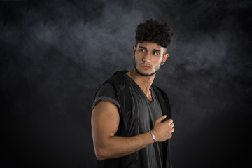 Handsome young man in dark t-shirt on black background