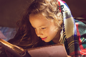 Vintage portrait of cute girl reading a book in cold day