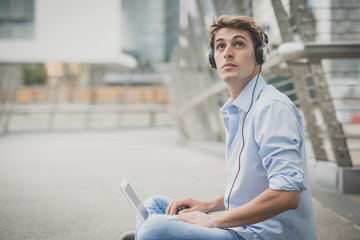 young model hansome blonde man with notebook and headphones