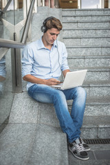 young model hansome blonde man headphone and notebook