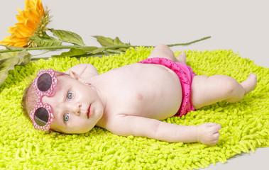 Beautiful little girl on green carpet