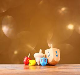 wooden dreidels for hanukkah and glitter golden lights backgroun