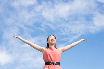 腕を広げる女性と空