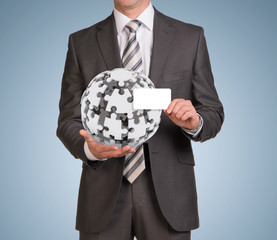 Man hold empty card and jigsaw puzzle sphere