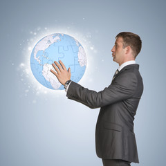Businessman in suit hold earth globe consisting of puzzles
