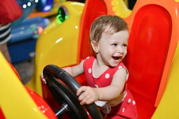 Little baby girl riding a car in amusement park