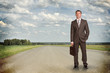 Businessman with briefcase standing on the road