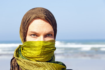 Beautiful arabic woman with green scarf at the ocean
