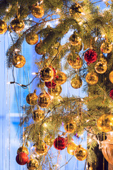 Variety of Christmas tree ornaments hanging on a Christmas tree.