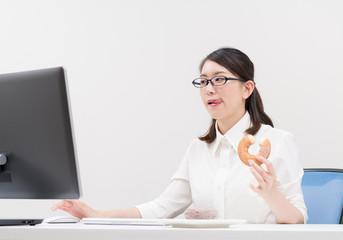 ドーナツを食べながら仕事する女性