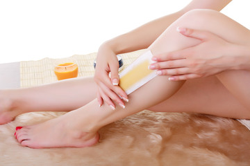 Girl doing depilation with wax on the feet.