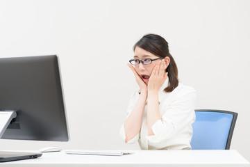 パソコンを見て驚く女性