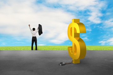 businessman cheering for free from dollar sign shackle