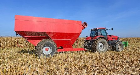 A tractor with a trailer to transport the grain to harvest corn