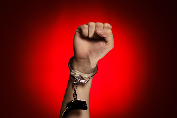 fist and handcuffs opened over red background