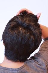 前髪をかき上げる30代の男性