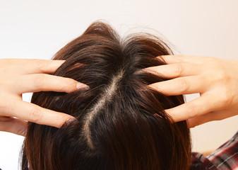 頭皮をマッサージする30代の女性