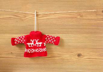 Red handmade sweater on wooden background