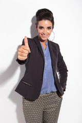 Beautiful business woman smiling while showing thumbs up