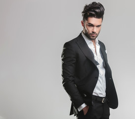 elegant young man in tuxedo looking down