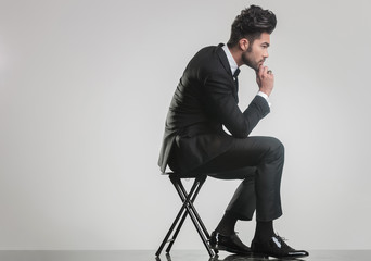 elegant young man sitting on a stool and thinking