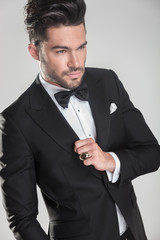 Angle view of an elegant young man ajusting his tuxedo