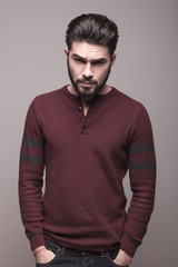 man in burgundy sweater holding his hands in pocket