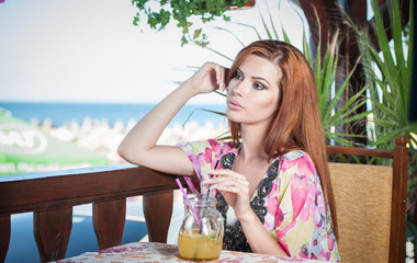 Attractive red hair young woman with bright colored blouse