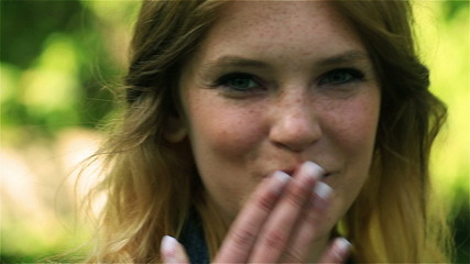 Girl sending sweet kiss and smiling to the camera, steadycam