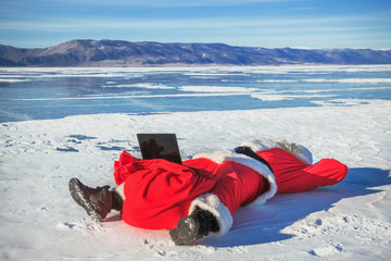Santa Claus lying on the snow, looking at laptop news