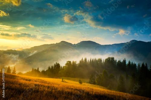 Leinwandbild Motiv Amazing mountain landscape with fog and a haystack