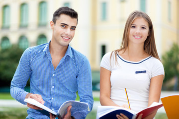 Portrait of two smiling students sitting out of the school