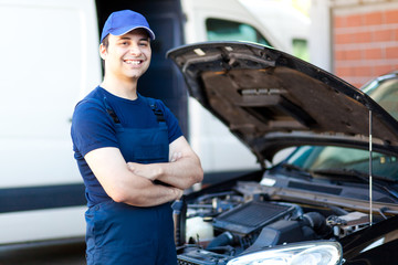 Smiling car mechanic at work