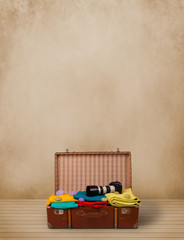 Retro tourist luggage with colorful clothes and copyspace