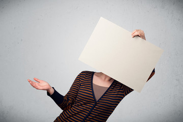 Woman holding in front of her head a paper with copy space