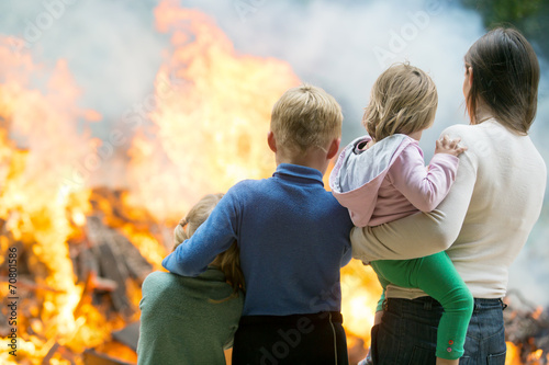 Leinwanddruck Bild Family mother with children at burning house background