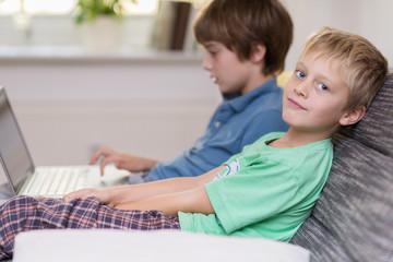 kinder mit laptop auf dem sofa
