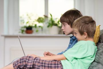 zwei jungen schauen auf laptop