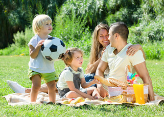 Young family with children having picnic outdoor