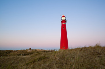 red lighthouse at sunset on island coast