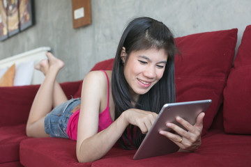 Young beautiful woman using computer tablet on red sofa