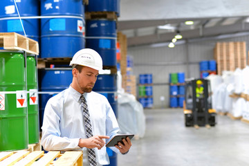 Manager of a logistics company with tablet in the warehouse