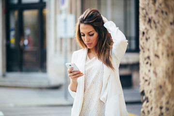 Young businesswoman using phone on street