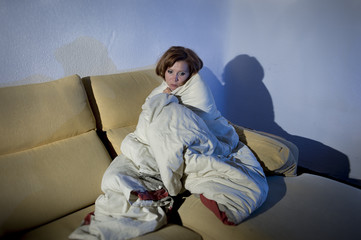 young sick woman on couch wrapped in duvet feeling miserable